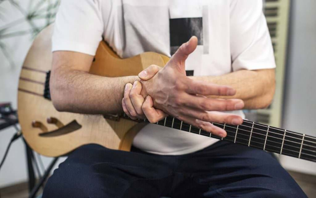man with wrist pain playing guitar