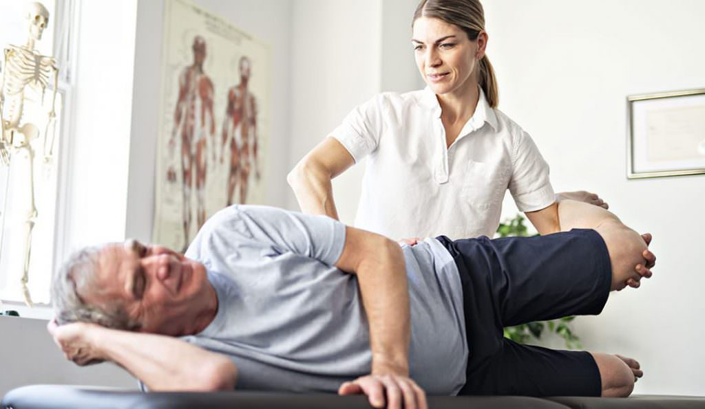 old man with back pain stretching