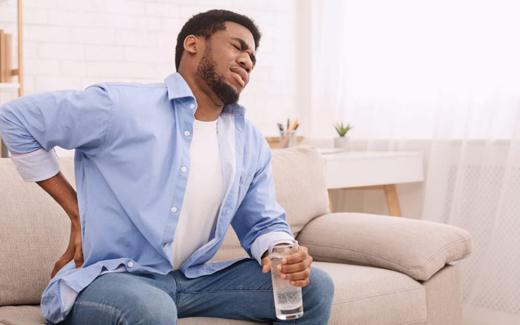 man sitting on couch with back pain
